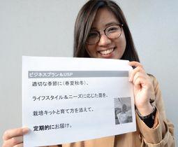 「野菜苗の定期お届け便」のレジュメを持ち笑顔の小野未花子さん