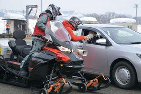 大雪による立ち往生を想定した対応訓練で、スノーモービルを使い車両に物資を配布する様子=28日午前、新潟県南魚沼市