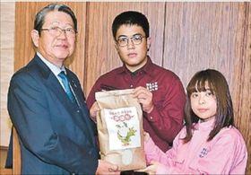 菅野会長に新米を手渡す塩村さん(中央)と磯田さん(右)