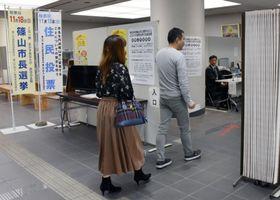 「丹波篠山市」への市名変更の賛否を問う住民投票と出直し市長選の投票のため投票所に入る人たち=18日午後、兵庫県篠山市役所