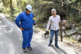 建設会社社員の中武潤哉さん(左)を撮影した後、談笑する小河さん=西米良村