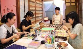 自宅で開くアルバム作り教室の受講生と談笑する香川さん(左から3人目)
