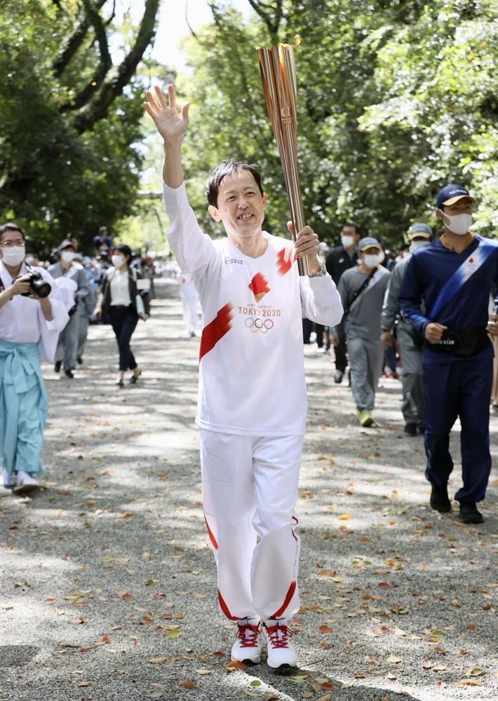 熱田神宮の参道を走る聖火ランナーの和田真人さん=5日午前、名古屋市(代表撮影)
