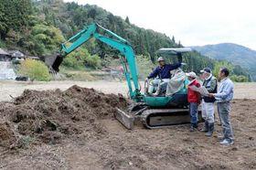 山に囲まれた市有地をグラウンドにする作業を進める佐古さん(左端)たち守る会メンバー