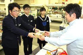 伊藤さん(右端)に手作りの募金箱を手渡す亀山さん(左端)