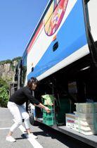 かぐや姫号のトランクに食品を積み込む西村さん
