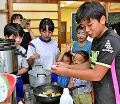 ラジオ体操後の時間を使ったアサカツで、一緒に朝食を作る小中学生