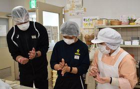 通所者(右)に作り方を教わりながら、クッキーを作る初任科生たち=長崎市、「わかばの里」