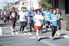 熊谷桜堤近くのコースを駆け抜けるランナー=24日、熊谷市