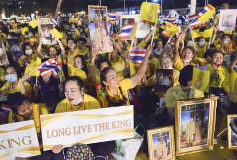 バンコクで開催された王室関連行事で、ワチラロンコン国王夫妻の写真を掲げる王室支持者ら=25日夜(共同)