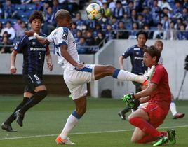 【大分|G大阪】前半25分、相手GKのクリアボールを体で押し込む大分のFWオナイウ(左から2人目)=パナソニックスタジアム吹田