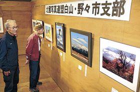 豊かな風景を捉えた作品に見入る来場者=白山市のJR美川駅