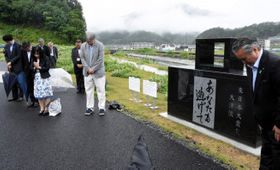「あなたも逃げて」と刻んだ碑をお披露目し、海に向かって黙とうする出席者ら=16日、釜石市鵜住居町