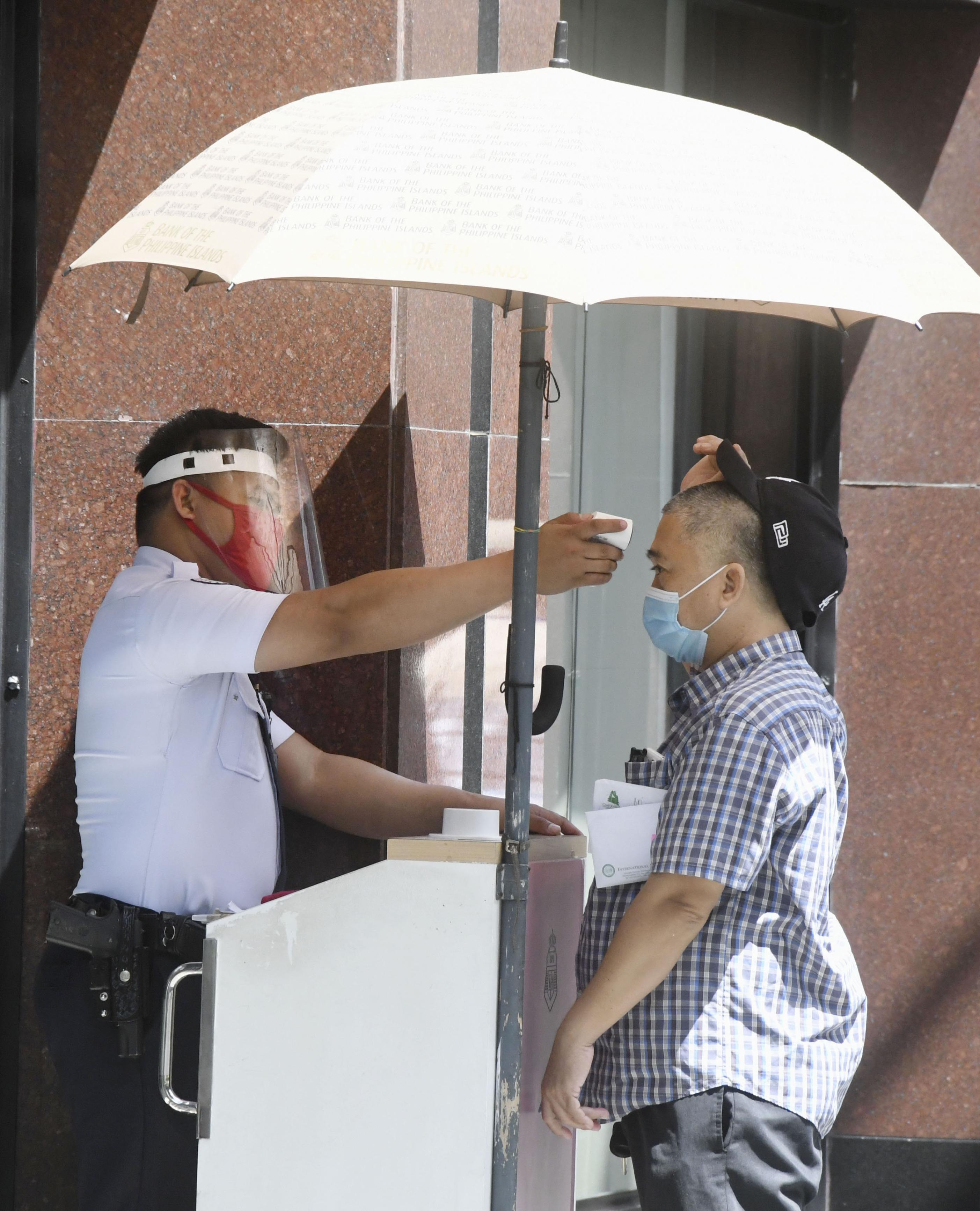 フィリピン・マニラのオフィスビル入り口で訪問者の体温を測る警備員=1日(共同)