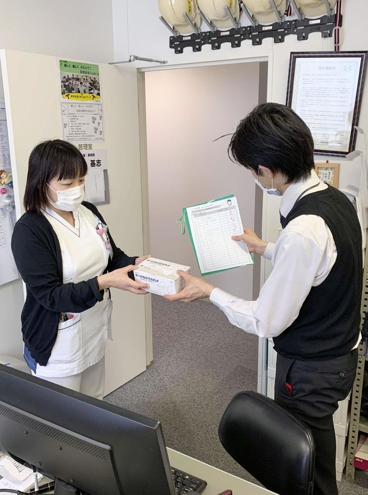 マスクが「配給制」となり、管理担当者(右)から受け取る病院職員=3月、東京都立川市の立川相互病院