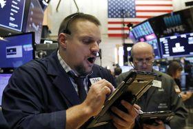 ニューヨーク証券取引所のトレーダー=19日(AP=共同)