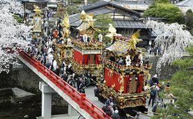 春の高山祭が開幕。満開の桜と共に赤い中橋を渡る祭り屋台=岐阜県高山市、宮川の中橋