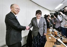 記者会見を前に笑顔で井戸謙一弁護士(左)と握手する西山美香さん=19日午後、大津市