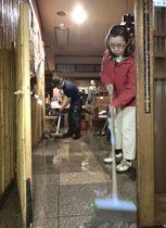 冠水した長崎市銅座町の飲食店で、店内の水をかき出す従業員ら=21日夜