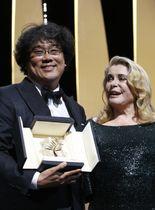 カンヌ国際映画祭授賞式、最高賞パルムドールを受賞し、プレゼンターのカトリーヌ・ドヌーブと笑みを浮かべるポン・ジュノ監督=25日、カンヌ(ロイター=共同)