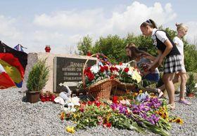 17日、ウクライナ東部ドネツク州で、マレーシア航空機の犠牲者の追悼碑を訪れる人々(ロイター=共同)