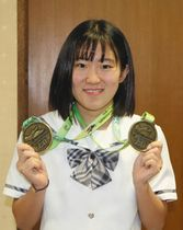 二つの銅メダルを手に笑顔の中東さん=松本市役所で