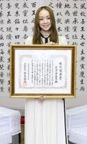 沖縄県から県民栄誉賞を贈られ、表彰状を手にする安室奈美恵さん=23日午後、沖縄県庁