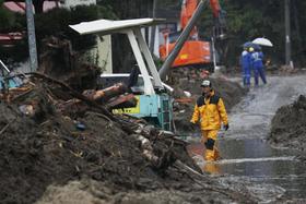 雨が降る宮城県丸森町の被災地で、水に漬かった道路を歩く人=22日午前10時40分