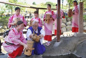「独鈷の湯」で僧侶から手おけに湯を受ける湯くみ娘たち=21日午後、静岡県伊豆市の修善寺温泉