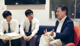 環境エネルギー政策研究所の飯田哲也所長(右)にインタビューする矢座孟之進さん(中央)ら=2018年10月、東京都新宿区