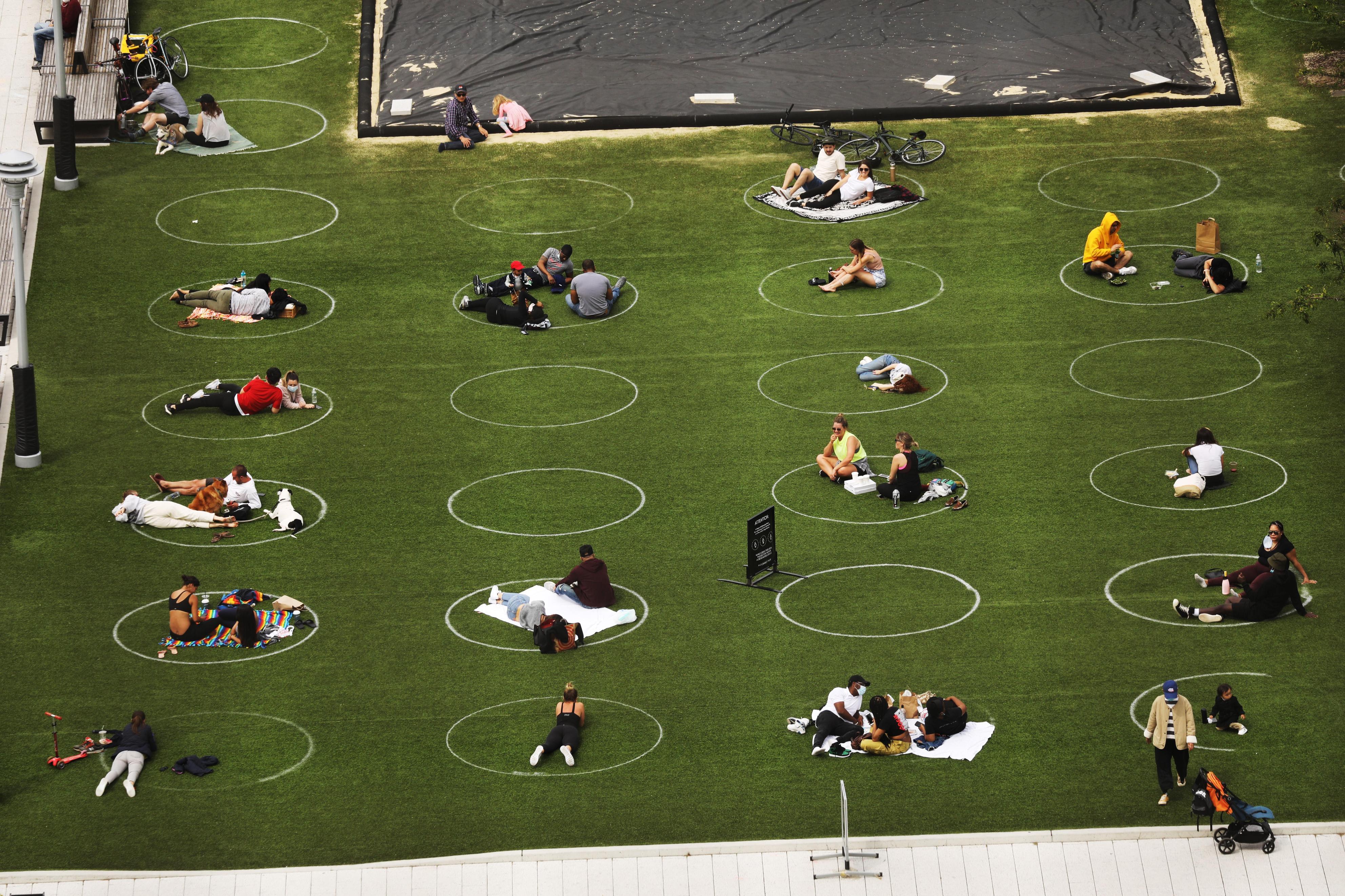 距離を保つための円の中に座る人々=18日、ニューヨーク(ゲッティ=共同)