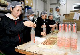 出荷前の作業を行う田村さん(左)ら女性社員