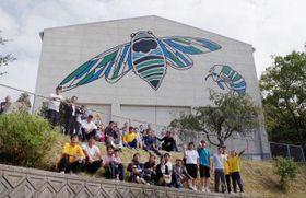 完成した壁画を背に記念撮影する岩中さん(前列右から5人目)と岩黒島の住民ら