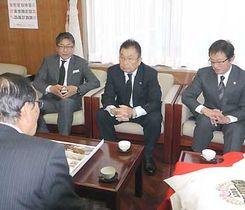 唐木村長(手前左)にリーグ優勝を報告する三沢会長(右から2人目)ら