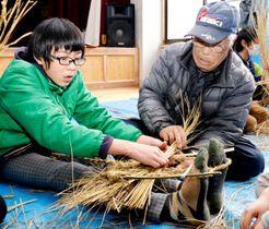 住民(右)と協力してわらの草履を編む児童
