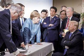 9日、カナダでのG7サミットでトランプ米大統領(右端)に向かい身を乗り出すドイツのメルケル首相(中央左)(ドイツ政府提供、AP=共同)
