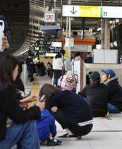 東北新幹線が緊急停車した影響で、ホームにしゃがみ込んで運行再開を待つ利用客=17日午後、JR仙台駅