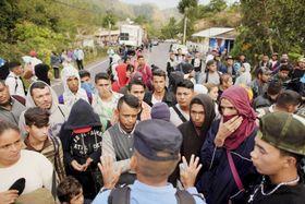 16日、中米ホンジュラスで、米国を目指してグアテマラへの入国許可を求める移民を落ち着かせようとする警察官(手前)(ロイター=共同)