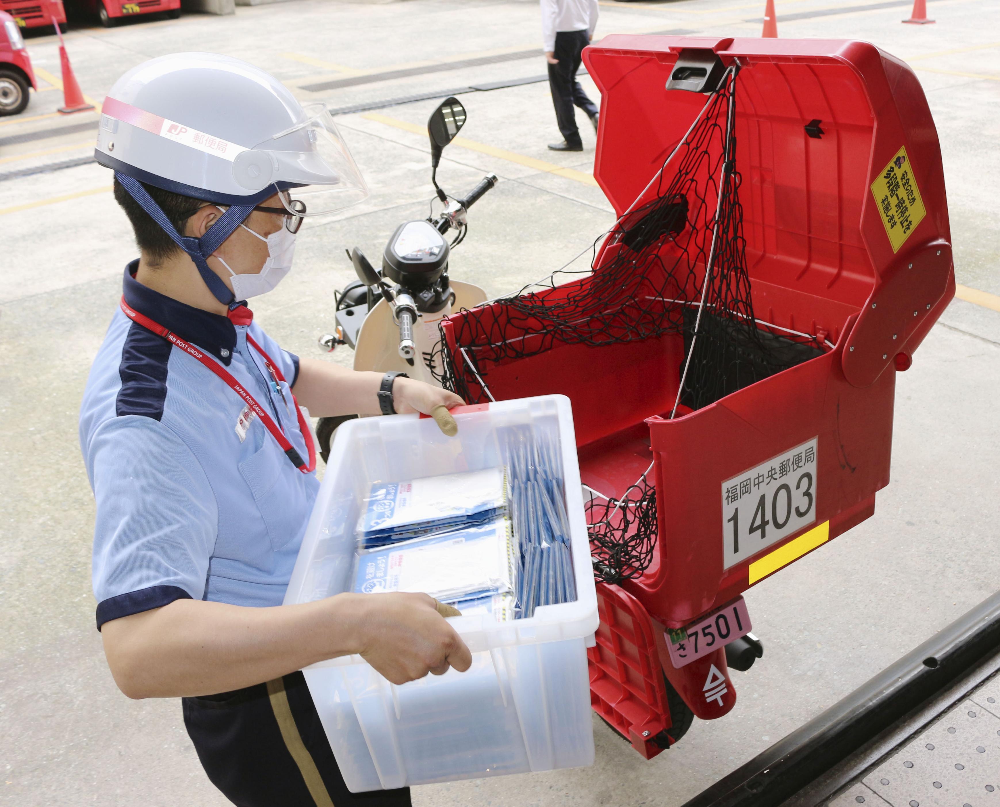政府が全世帯に配布する布マスクをバイクに積み込む郵便局員=12日午前、福岡市中央区