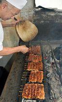 たれをつけたウナギを手際よく焼く職人=19日午前、青森市本町の「川よし」