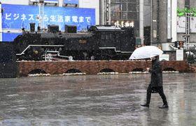 雪が降る中、JR新橋駅前を歩く人=29日午前8時51分