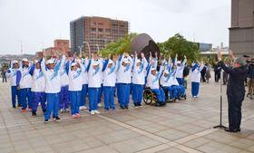 福井県で開かれる全国障害者スポーツ大会での健闘を誓って万歳する鹿児島県選手団=鹿児島県庁