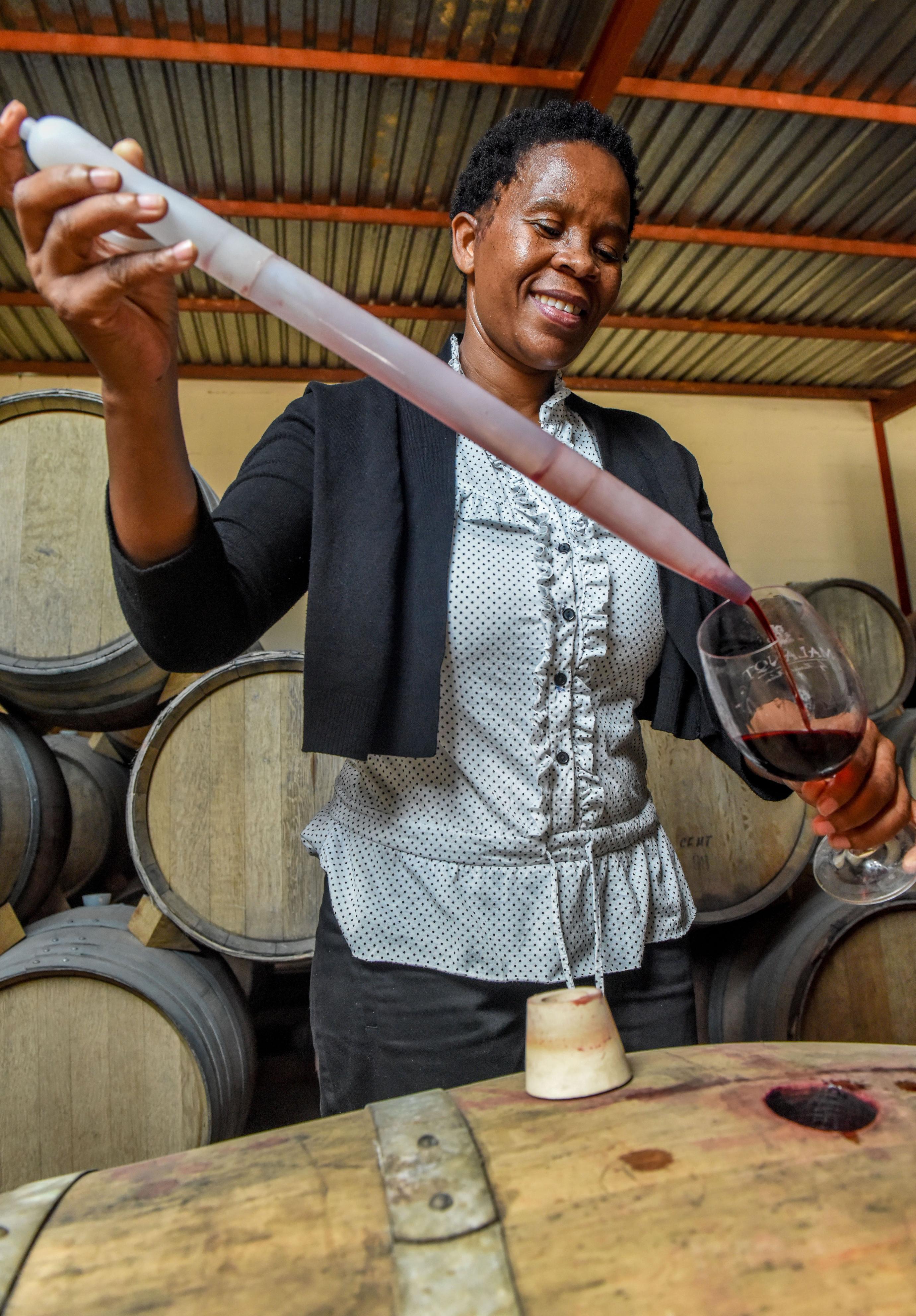 仕込んだワインを試飲するため、樽から取り出す黒人女性醸造家の先駆者、ヌツィキ・ビエラ=ステレンボッシュ