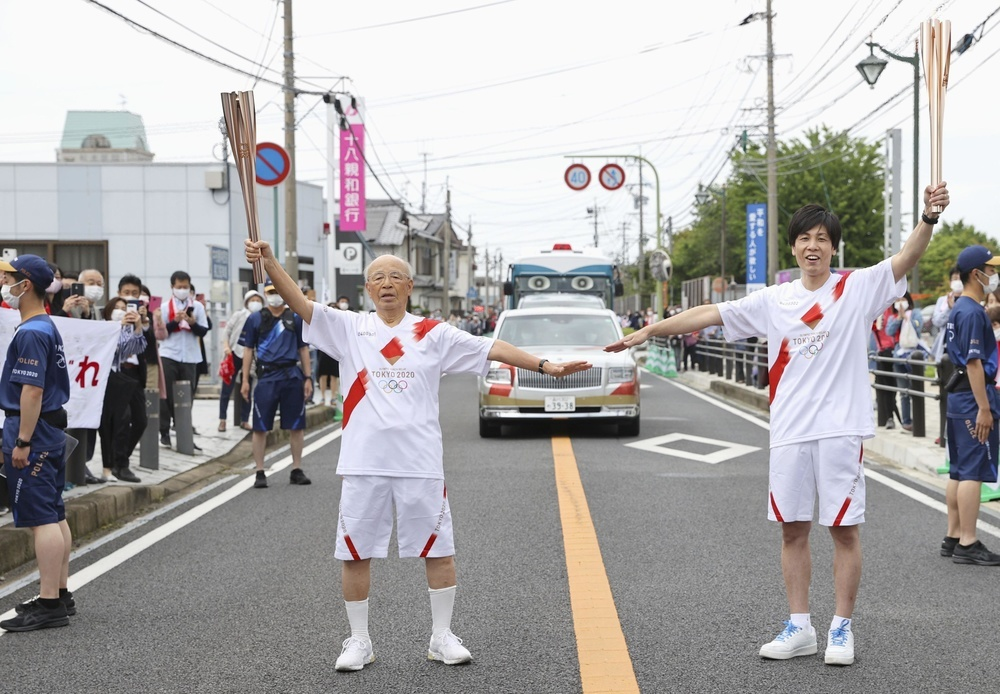 長崎新聞代表撮影、境佑介さん(右)に聖火を引き継ぎ、ポーズをとる宮田隆さん=7日午後、長崎県雲仙市