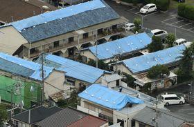 地震で被災し、屋根がブルーシートで覆われた建物=19日午後、大阪府高槻市(共同通信社ヘリから)