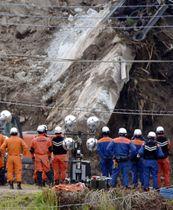 山崩れに巻き込まれた行方不明者の捜索を見守る消防隊員ら=20日午後、大分県中津市耶馬渓町