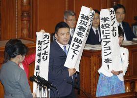 カジノを含む統合型リゾート施設整備法の投票で、主張を書いた紙を掲げる自由党の山本共同代表(中央)ら=20日午後、参院本会議場