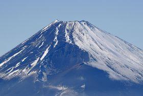 18日、静岡県三島市上空から見た富士山。斜面の右側は雪で覆われ、左側は岩肌が露出している(共同通信社ヘリから)