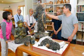 西日本豪雨の被害を受けた仏像の修理方針を話し合う長谷川さん(右端)、中田統括学芸員(左端)ら=13日、赤磐市