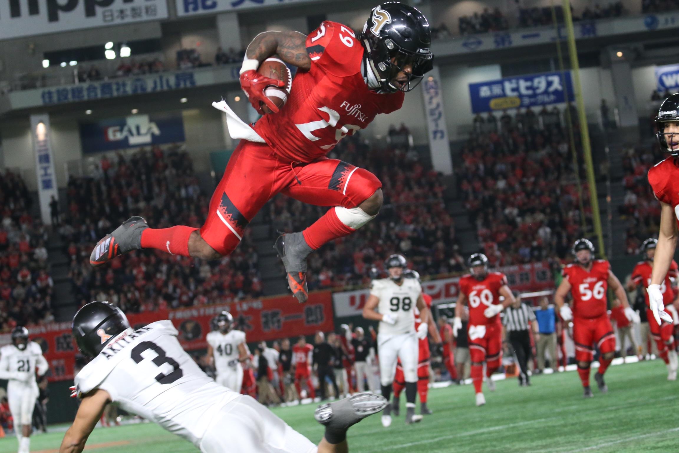 相手の守備選手を飛び越えて前進する富士通のRBグラント(29)=撮影:武部真